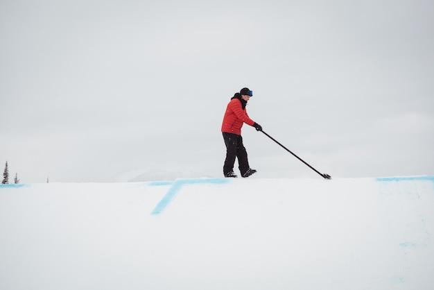 Mann, der schnee im skigebiet reinigt