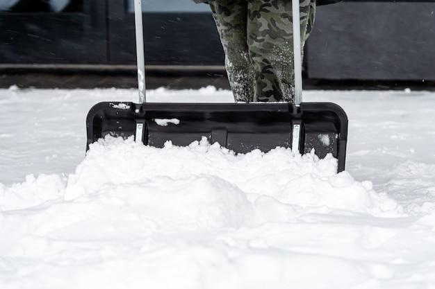 Mann, der schnee in einem hinterhof nach einem schneesturm schaufelt, nahaufnahme