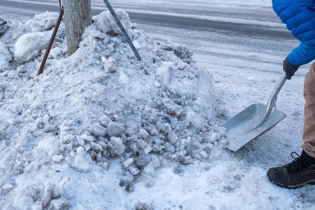 Mann, der schnee mit schaufel auf straßenrand reinigt