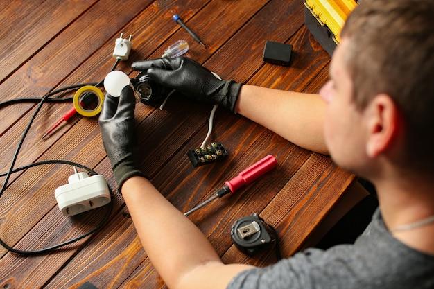 Mann, der schreibtischlampendrähte draufsicht festhält. elektriker repariert lichter. techniker service arbeitsplatzkonzept. werkzeuge und instrumente auf dem tisch. männliche hände, die elektronische gebrochene teile, details halten. hoch