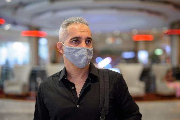 Mann, der schützende gesichtsmaske trägt, um innerhalb des einkaufszentrums vor dem covid-19-corona-virus zu schützen