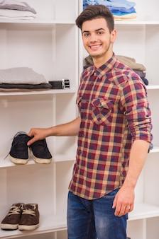 Mann, der schuhe in der umkleidekabine und im lächeln wählt