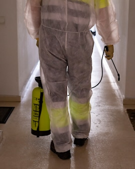 Mann, der schutzanzug desinfiziert, der öffentliche plätze in der sonne mit chemikalien desinfiziert, um ausbreitung des coronavirus, pandemie in der quarantänestadt zu verhindern. covid 19. reinigungskonzept.