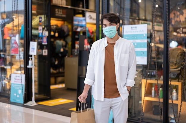 Mann, der schutzgesichtsmaskeneinkauf am supermarkt, neuer normaler lebensstil trägt.