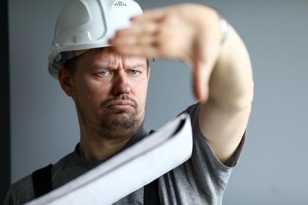 Mann, der schutzhelmgriff in den händen hält, die baustelle steuern