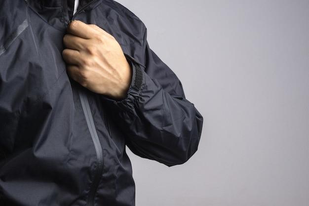 Mann, der schwarze antistatische oder regenjacke oder regenmantel trägt