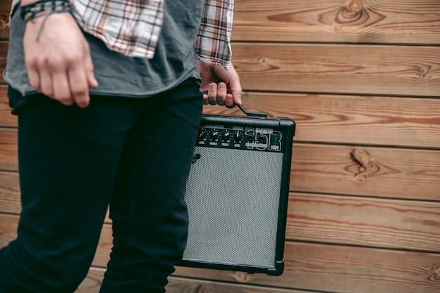 Mann, der schwarzen elektrischen gitarrenverstärker für musiker hält