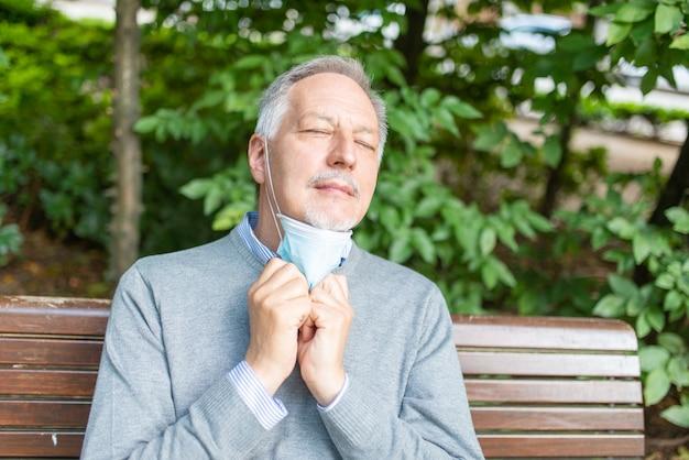 Mann, der schwierigkeiten hat, mit seiner maske zu atmen, coronavirus-prävention in heißem klima konzept