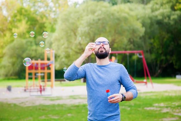 Mann, der seifenblasen im park nahe dem spielplatz bläst.