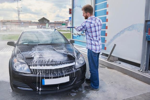 Mann, der sein auto in einer selbstbedienung putzt
