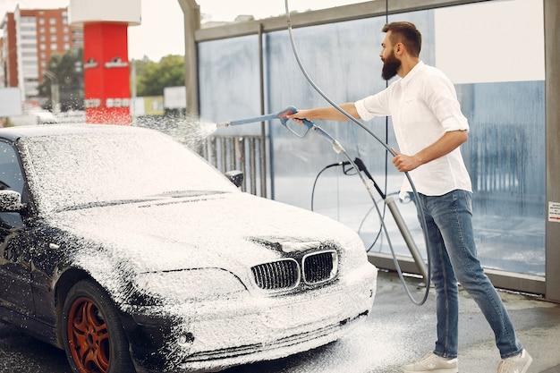 Mann, der sein auto in einer waschstation wäscht