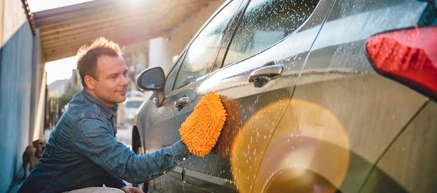 Mann, der sein auto mit waschhandschuh wäscht