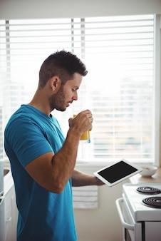 Mann, der sein digitales tablett beim glas saft verwendet