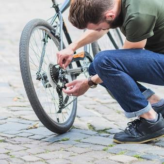 Mann, der sein fahrrad auf straße repariert