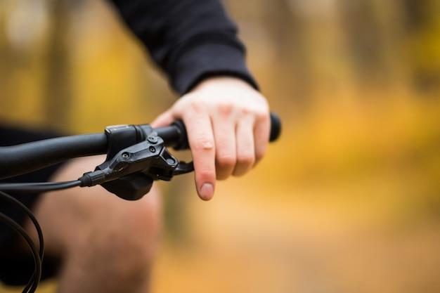 Mann, der sein fahrrad durch einen park auf einem weg entlang einer bunten schiene fährt, nahaufnahme auf seinem handrücken am lenker