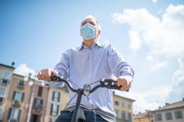 Mann, der sein fahrrad in einem stadtplatz reitet, während eine covid coronavirus maske trägt