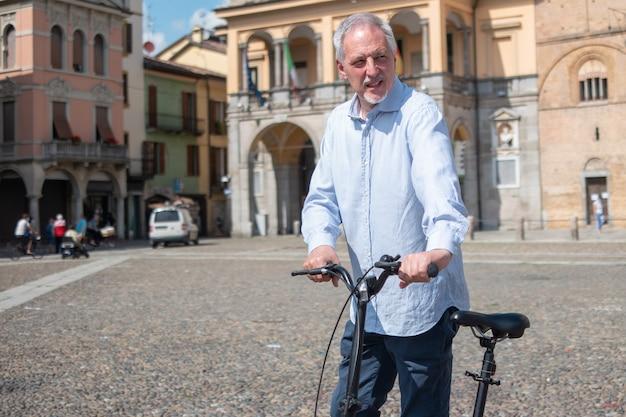 Mann, der sein fahrrad in einem stadtplatz reitet