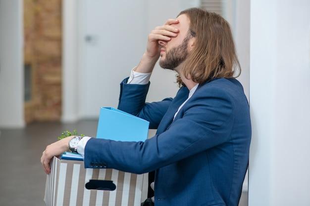 Mann, der sein gesicht mit seiner hand bedeckt, während er mit einer schachtel persönlicher gegenstände im bürokorridor sitzt