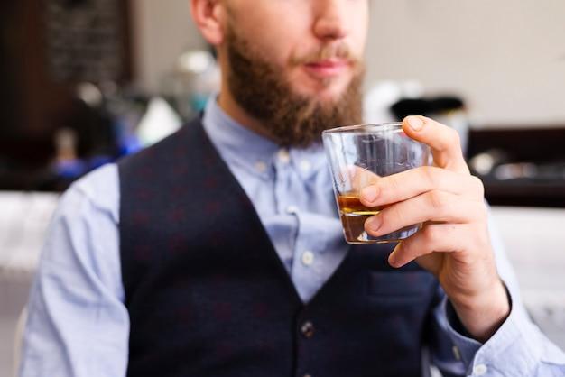 Mann, der sein getränk am friseursalon hält
