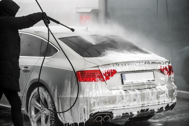 Mann, der sein graues auto unter hochdruckwasser im freien wäscht. - rückansicht