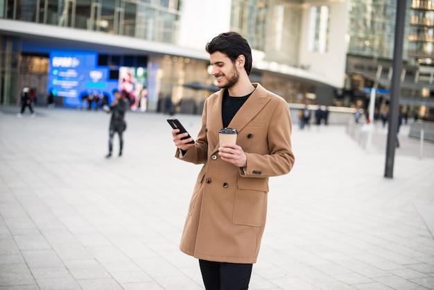Mann, der sein handy benutzt und eine tasse kaffee hält, während er in einer stadt geht