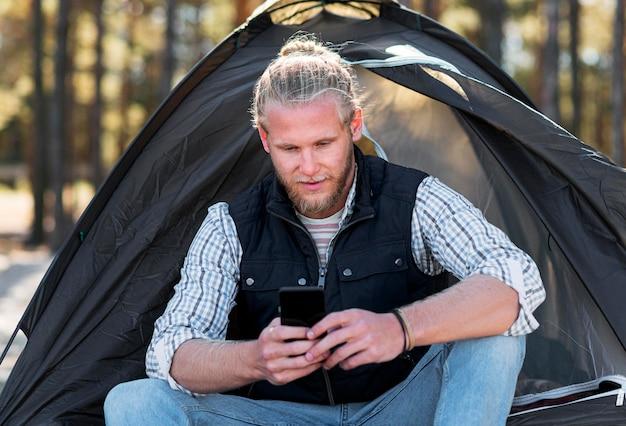 Mann, der sein handy vor dem zelt benutzt