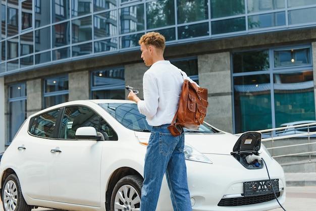 Mann, der sein luxuriöses elektroauto an der außenstation vor modernen neuen stadtgebäuden auflädt