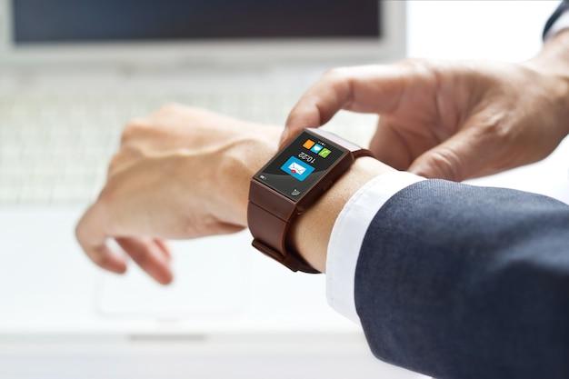 Mann, der sein smartwatch auf laptophintergrund verwendet