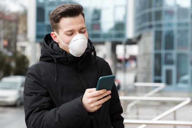 Mann, der sein telefon beim tragen der medizinischen maske betrachtet
