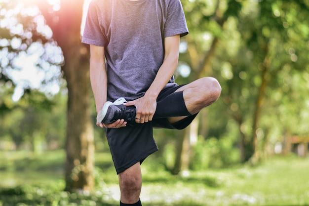 Mann, der seine beinmuskeln vor dem training ausdehnt, junges männliches joggersportlertraining