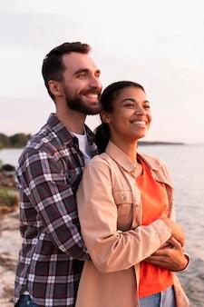 Mann, der seine freundin von hinten umarmt, während er den sonnenuntergang betrachtet