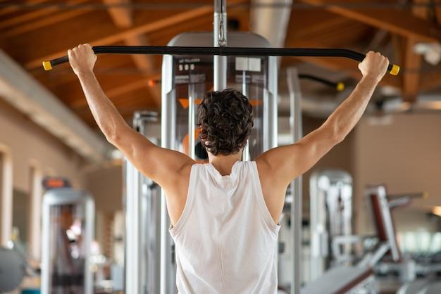 Mann, der seine schultern und zurück in einem fitnessstudio trainiert