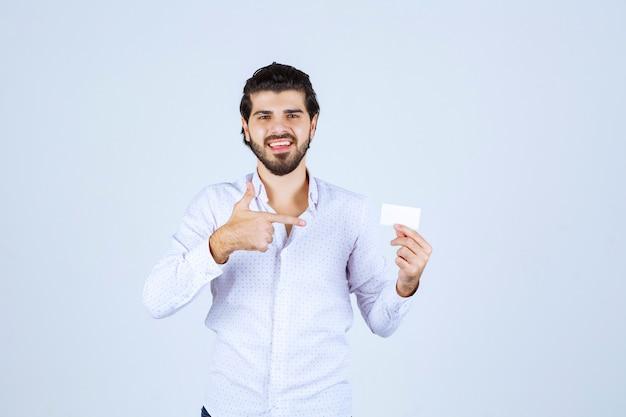 Mann, der seine visitenkarte hält und seinen erfolg meint