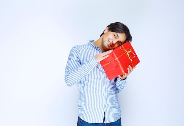 Mann, der seine wertvolle rote geschenkbox umarmt. foto in hoher qualität