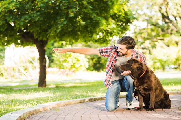 Mann, der seinem hund etwas im park zeigt