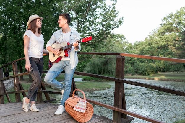 Mann, der seinem mädchen auf einer brücke gitarre spielt
