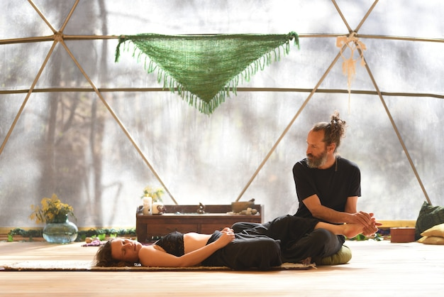 Mann, der seinem partner massage gibt, der auf einer geodätischen kuppel liegt