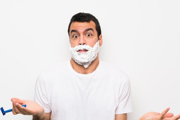 Mann, der seinen bart über der lokalisierten weißen wand macht zweifel rasiert, gestikulieren