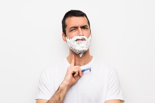 Mann, der seinen bart über der lokalisierten weißen wand schaut front rasiert