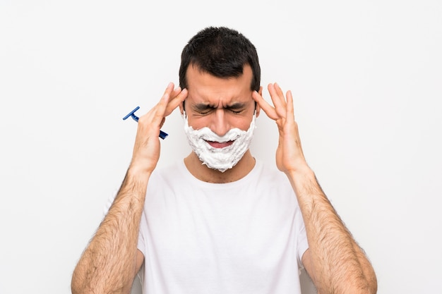 Mann, der seinen bart über lokalisierter weißer wand mit kopfschmerzen rasiert