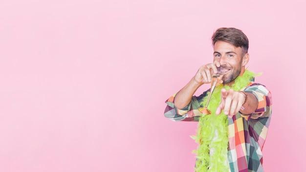 Mann, der seinen finger beim trinken des weins auf rosa hintergrund zeigt