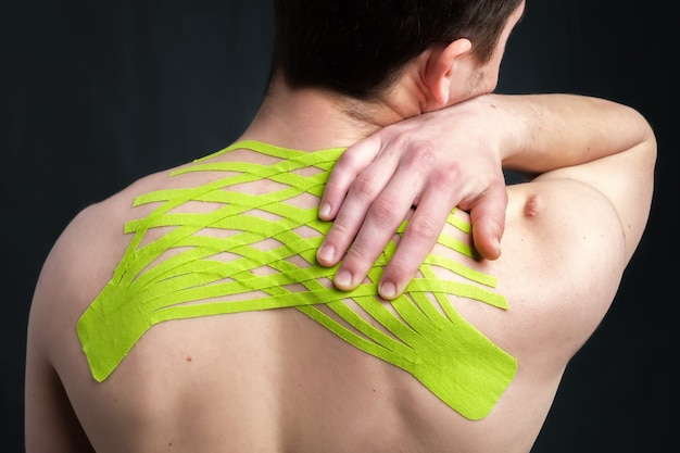 Mann, der seinen hals mit kinesiologischem medizinischem klebeband hält, das angewendet wird, um rückenschmerzen zu lindern