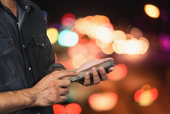Mann, der seinen Handy-Nachtlicht bokeh Hintergrund verwendet