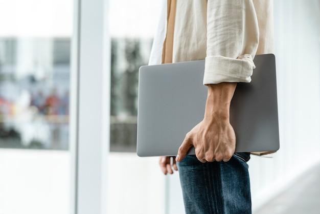 Mann, der seinen laptop beim gehen in der stadt trägt