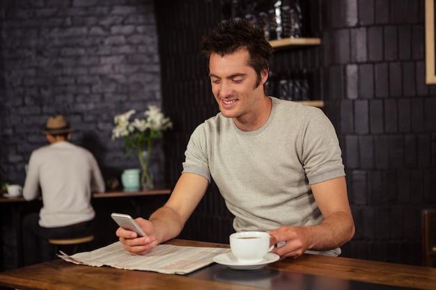 Mann, der seinen smartphone verwendet und kaffee trinkt