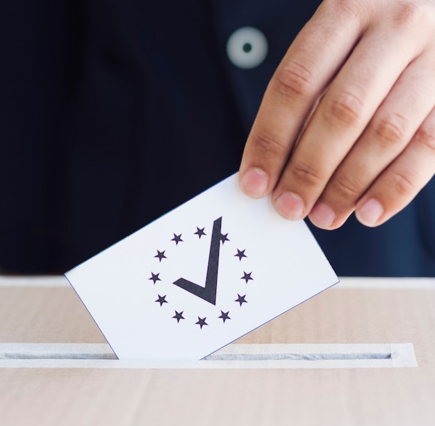 Mann, der seinen stimmzettel in eine kastennahaufnahme einsetzt