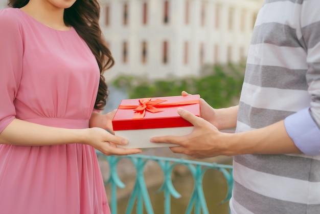 Mann, der seiner frau ein geschenk gibt. asiatisches paar verliebt im freien