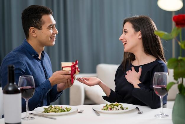 Mann, der seiner frau ein geschenk zum valentinstag gibt