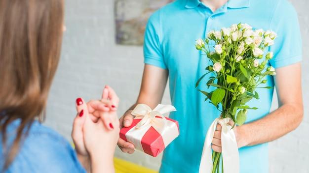 Mann, der seiner frau valentinsgrußgeschenk und -blumen gibt