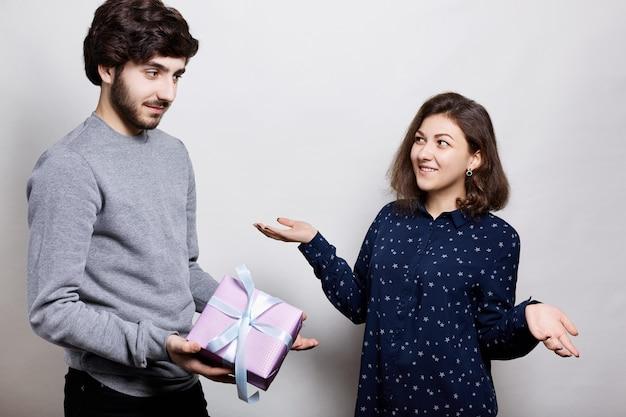 Mann, der seiner freundin ein geschenk gibt. romantische überraschung, frau erhält ein geschenk von ihrem freund